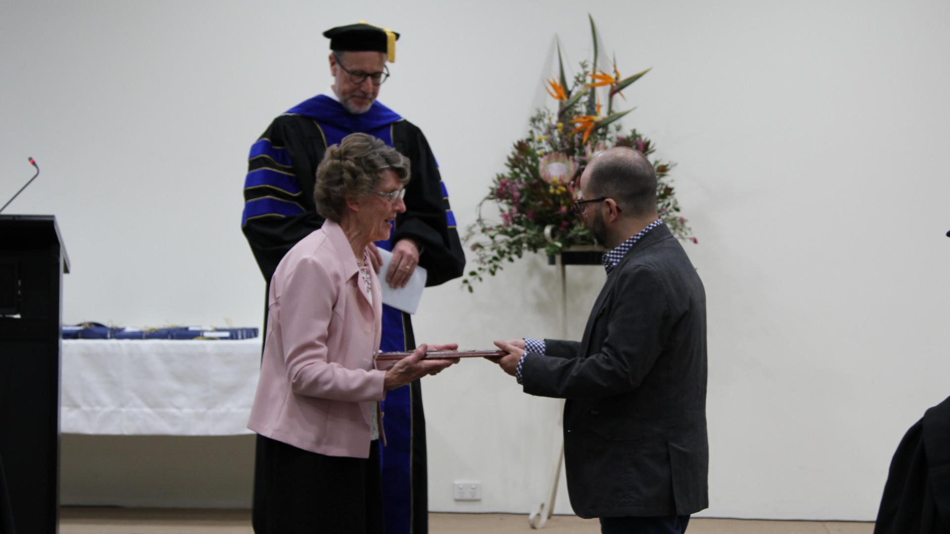 Andrew Grace receiving award from Margaret Rickard