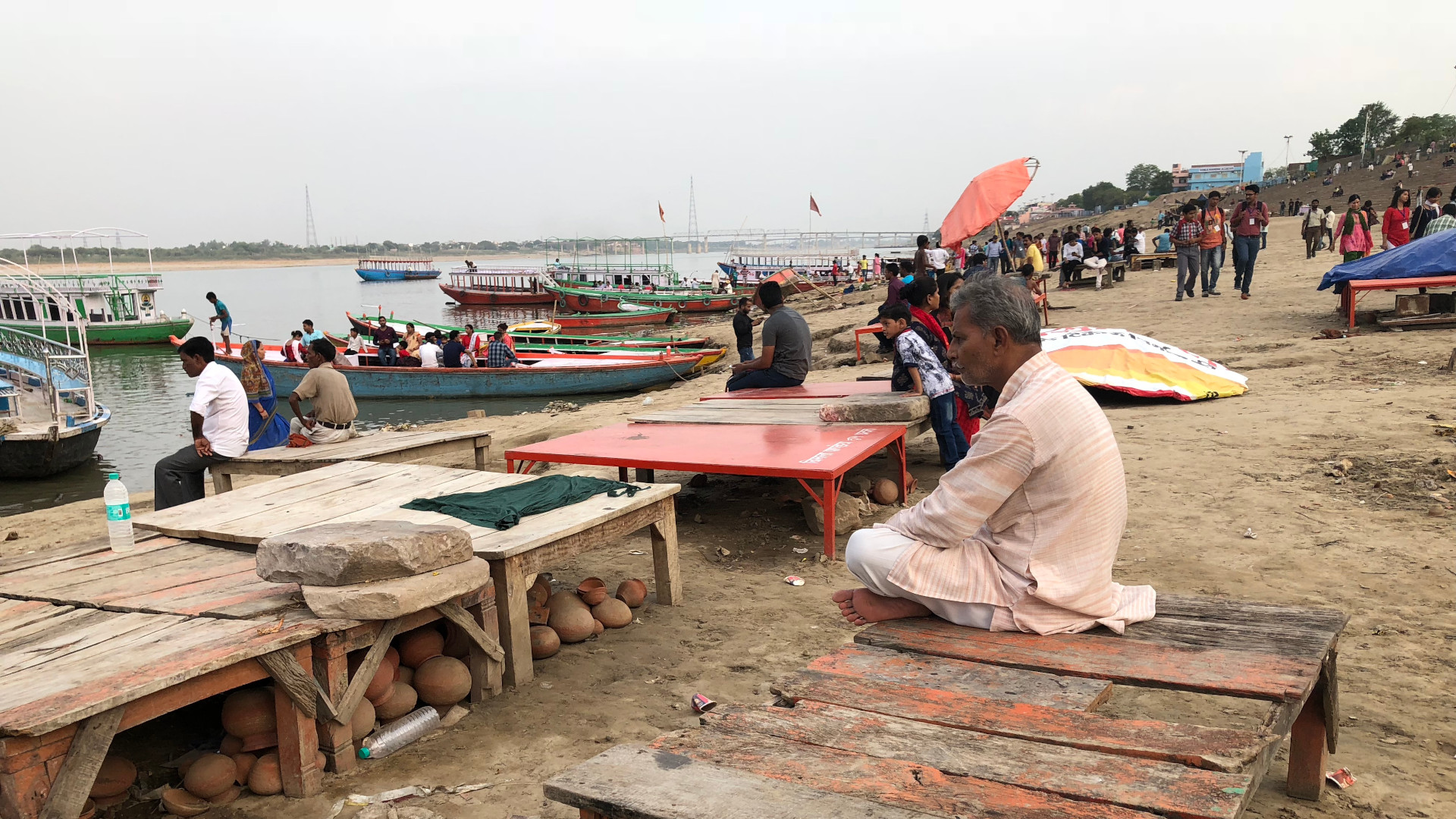 An Indian man sitting facing the river Ganges