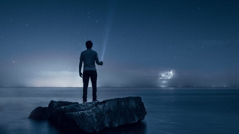 Man Standing on rock holding a flashlight