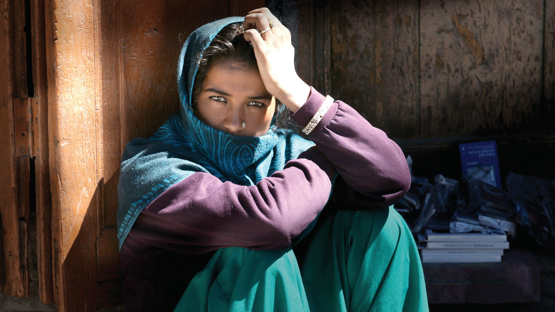 Middle eastern lady sitting with her face covered by a scarf