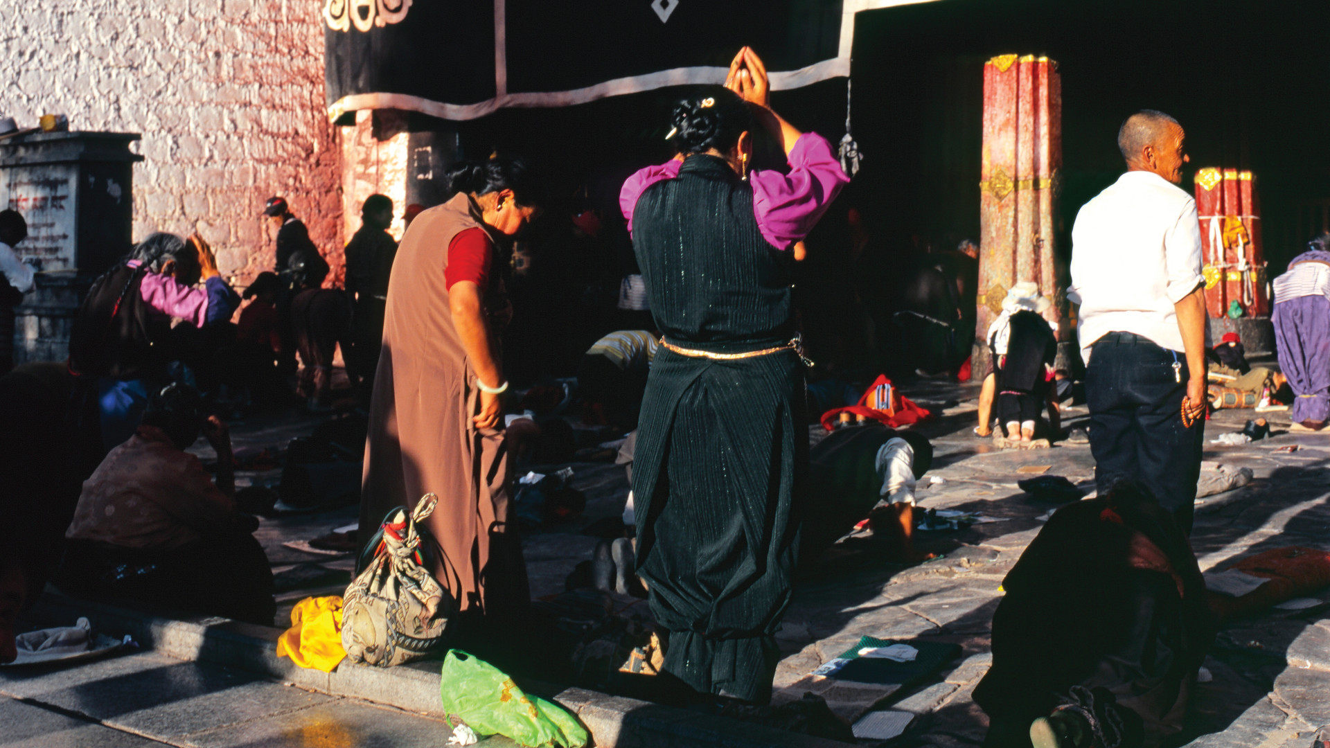 Two women praying amongst other worshipers